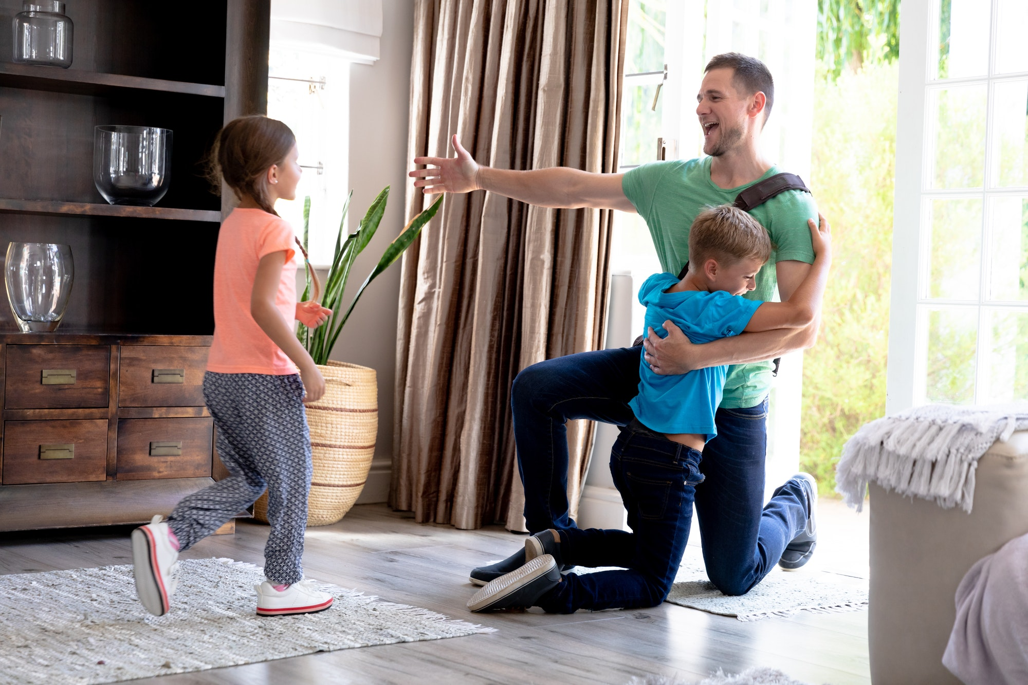 Caucasian girl and boy welcoming their father in their house.