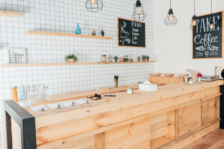 wooden bar counter of modern cafe decorated with white tiles