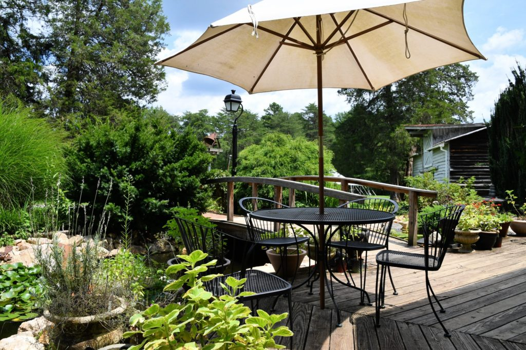 A cozy backyard outdoor living space with a table and umbrella on a deck next to a pond landscaping