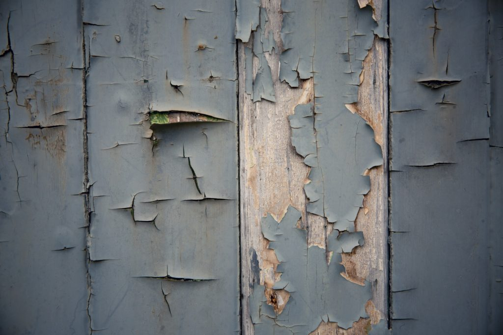 A worn and weathered texture background of flaked blue paint and rotting wood