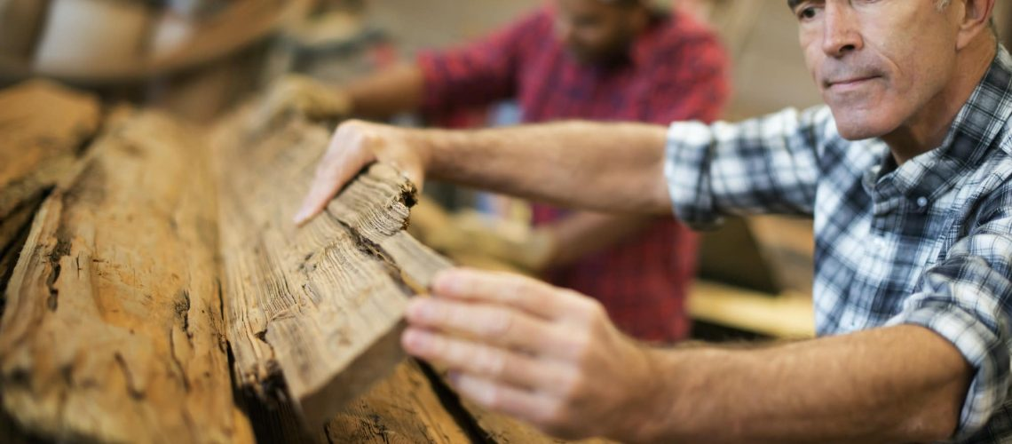 A reclaimed lumber workshop, man measuring and checking planks of wood for re-use and recycling