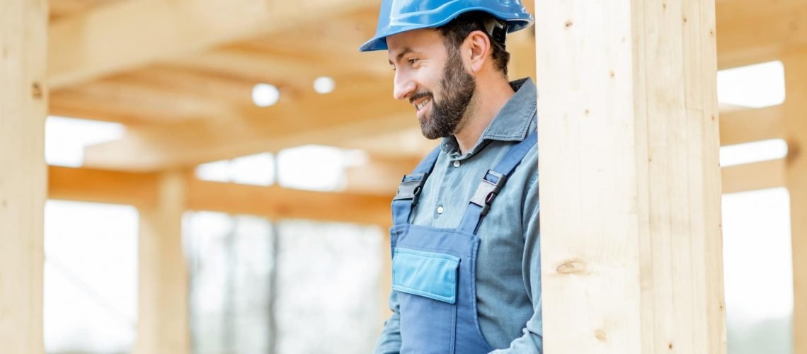 Builder on the wooden house structure