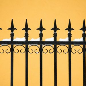 old fashioned spike fence against yellow wall, some snow